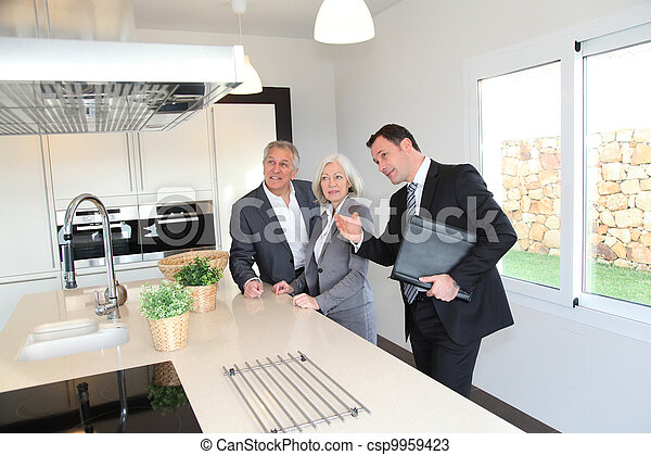 Real-estate agent showing interior of house to senior couple - csp9959423