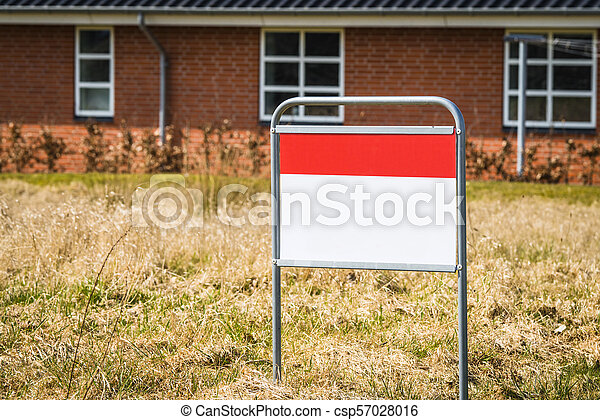 Real estate sign on a lawn in front of a house - csp57028016