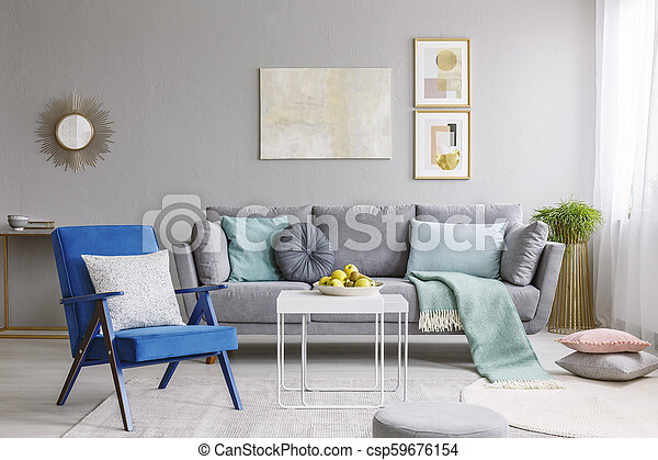 Real Photo Of A Blue Armchair Standing Next To A White Table In A Modern Living Room Interior With A Grey Sofa And Posters
