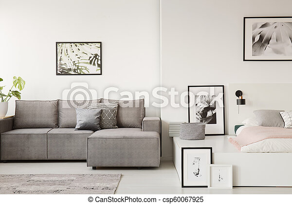 Real Photo Of A Grey Sofa With Cushions Standing Next To A White Platform Bed In Monochromatic Small Flat Interior With Posters On The Walls