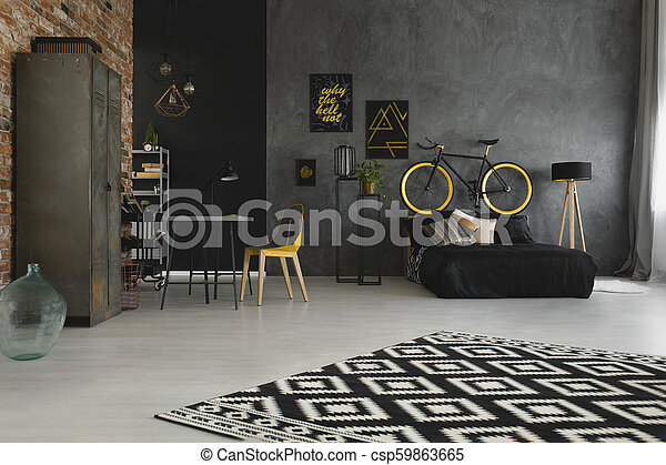 Enjoyable Real Photo Of A Spacious Bedroom And Study Space With Wooden Lamp Desk Yellow Chair Black Bed And Bike In Open Space Apartment Interior Pabps2019 Chair Design Images Pabps2019Com