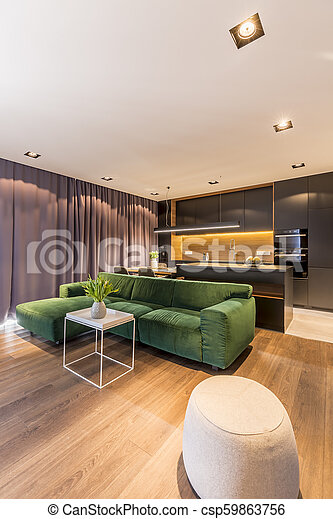 Real photo of green corner sofa and white end table with fresh tulips in  vase in modern living room interior with kitchen corner
