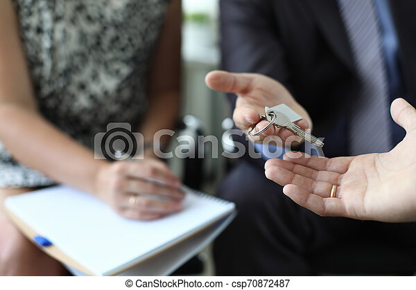 Realtor is handing over key of new apartment - csp70872487