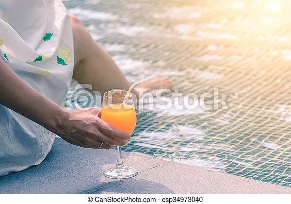 Rear view of beautiful woman in hat is holding orange juice glass at poolside in summer. - csp34973040