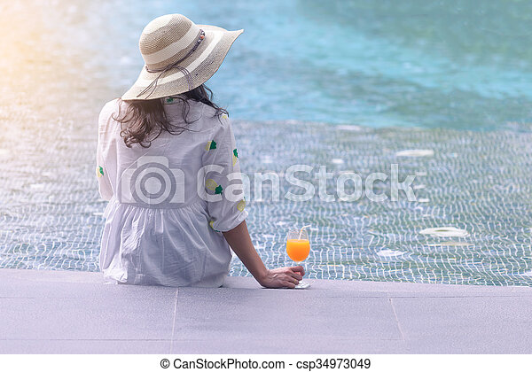 Rear view of beautiful woman in hat is holding orange juice glass at poolside in summer. - csp34973049