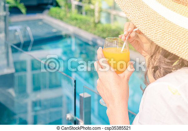 Rear view of beautiful woman in hat is drinking orange juice glass at poolside in summer. - csp35385521