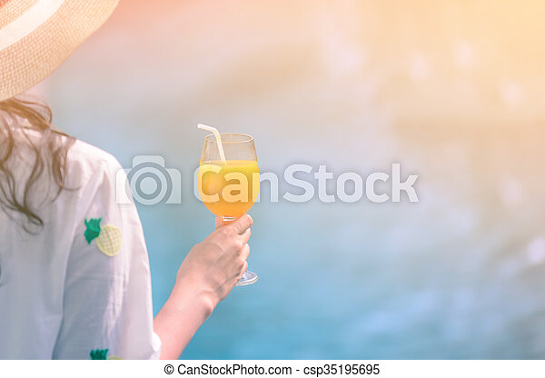 Rear view of beautiful woman in hat is holding orange juice glass at poolside in summer. - csp35195695