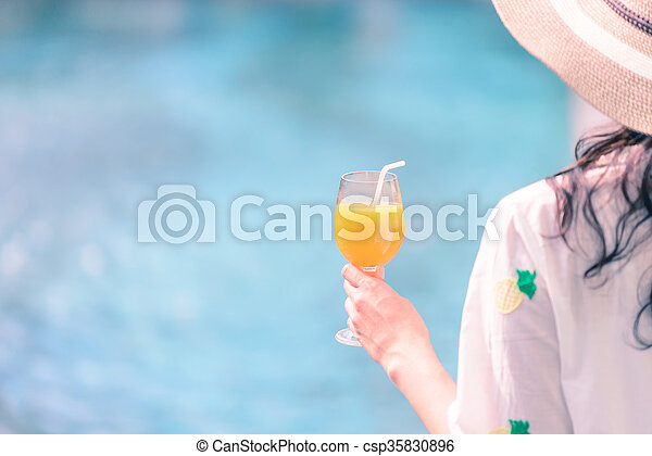 Rear view of beautiful woman in hat is holding orange juice glass at poolside in summer. - csp35830896