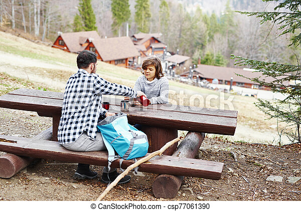 Rear view of hiker pouring his son some hot tea - csp77061390