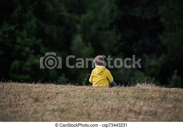 Rear view of school child sitting on field trip in nature, resting. - csp73443231