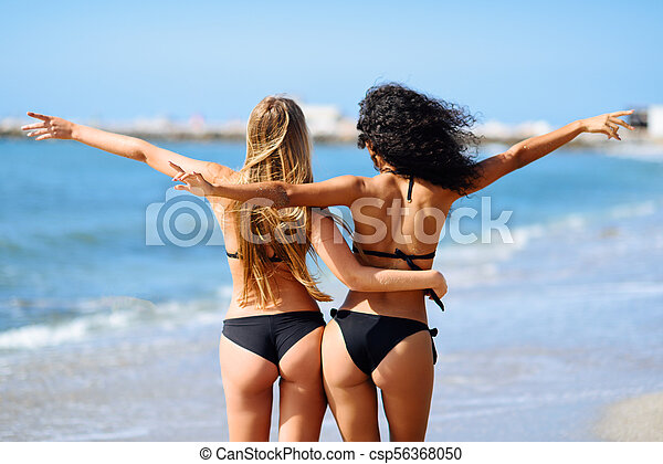 ce01819ff4cf7 Rear view of two young women with beautiful bodies in bikini having fun on  a tropical beach. girls with open arms.