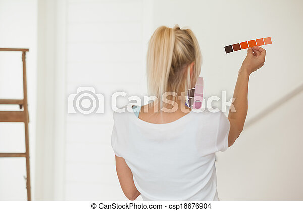 Rear view of woman choosing color for painting a room - csp18676904