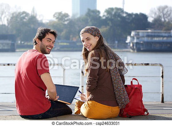 Rear view portrait of two college students smiling  - csp24633031