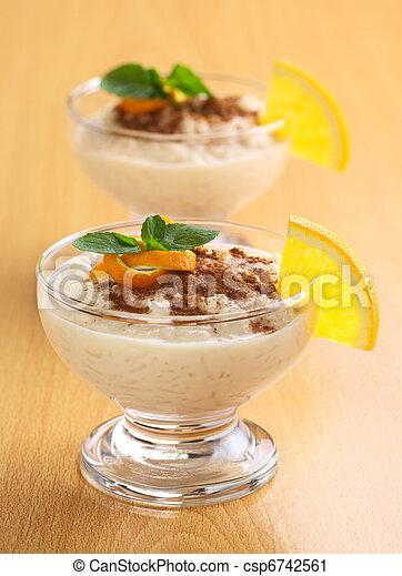Delicioso pudín de arroz casero con canela adornado con cáscara de naranja y hojas de menta y una rebanada de naranja en el borde del tazón (Concéntrese en la cáscara de naranja y la hoja de menta también - csp6742561