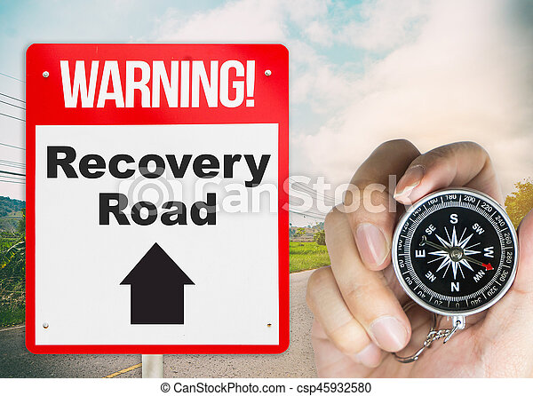 Recovery Road concept sign with holding compass for direction - csp45932580