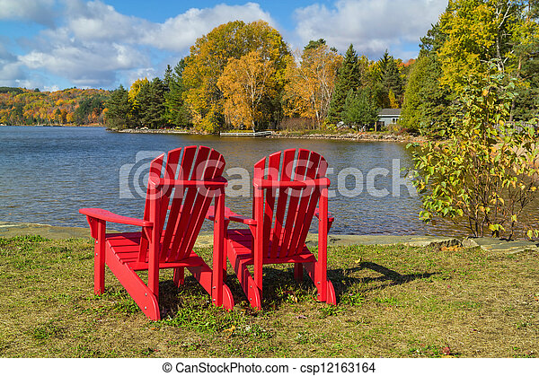 Red Adirondack Chairs on a Lake Shore - csp12163164