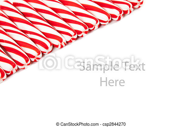 Red and white candy canes on white with copy space - csp2844270