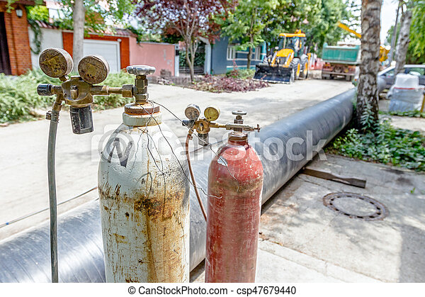 Red and white metal steel gas container with high pressure gauge meter and  valves