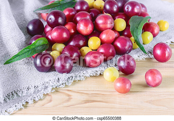 Red and yellow ripe plums on the table. - csp65500388