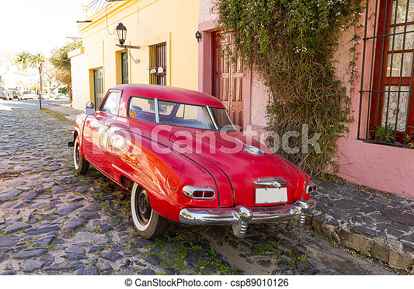 Red automobile on one of the cobblestone streets, in the city of Colonia del Sacramento, Uruguay. It is one of the oldest cities in Uruguay. - csp89010126