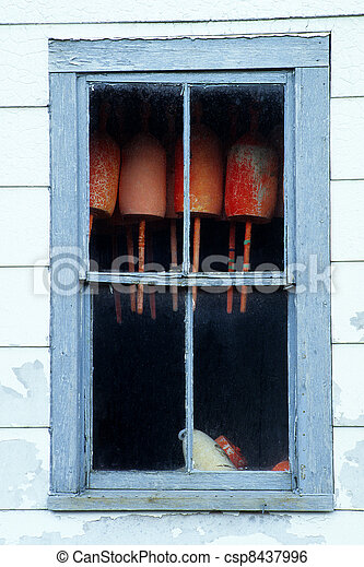 Red bouys haning inside an old window - csp8437996