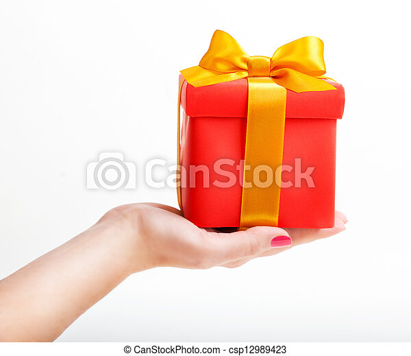 Red box with yellow ribbon in hand - csp12989423