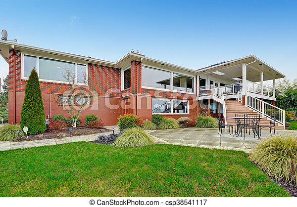 Red brick house with tile roof. Back yard - csp38541117