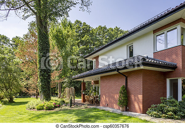 Red brick wall of house with roof and windows next to trees and garden - csp60357676