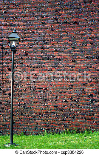 Red brick wall with lamp - csp3384226