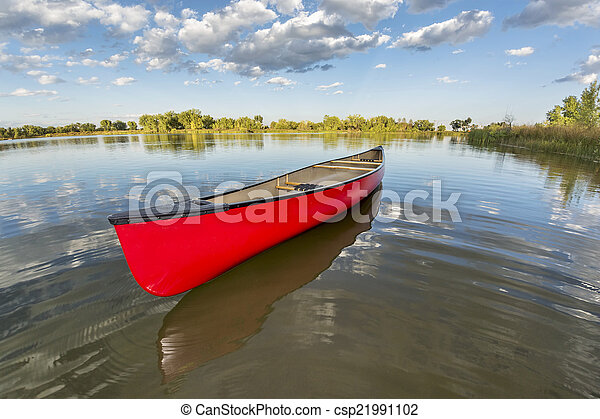 red canoe on a calm lake - csp21991102