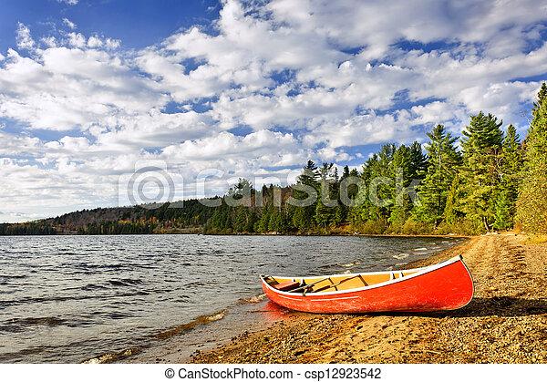 Red canoe on lake shore - csp12923542