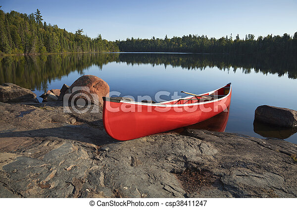 Red Canoe on Rocky Shore of Calm Lake with Pine Trees - csp38411247