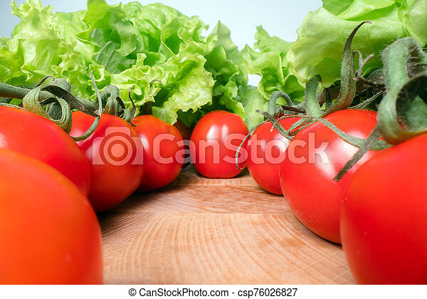 Red cheery tomatoes with lettuce leafs on top of wooden table background. Home grown vegetables, healthy eating lifestyle - csp76026827