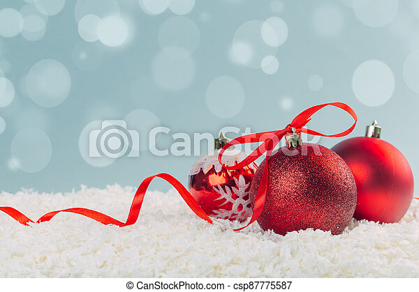 red Christmas ball with a scarlet satin bow in the snow on a blue background with bokeh lights. happy new year card - csp87775587
