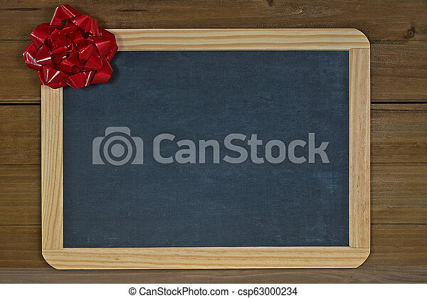 red Christmas bow on chalkboard - csp63000234