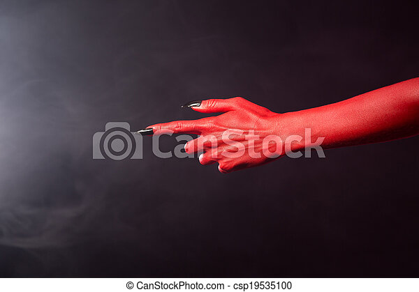 Red devil pointing hand with black sharp nails, extreme body-art, Halloween theme - csp19535100