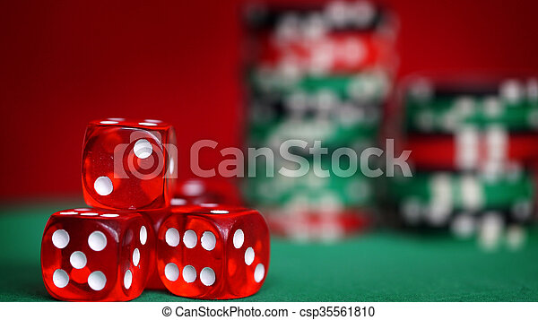 Red dice and casino chips on green table - csp35561810