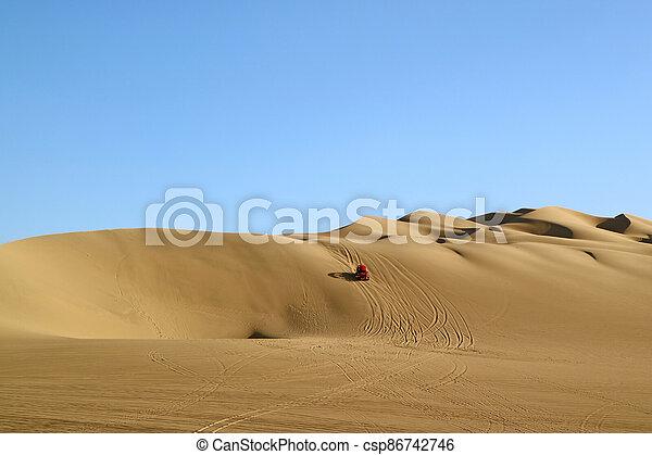 Red dune buggy running on the immense sand dune of Huacachina, Ica region, Peru - csp86742746