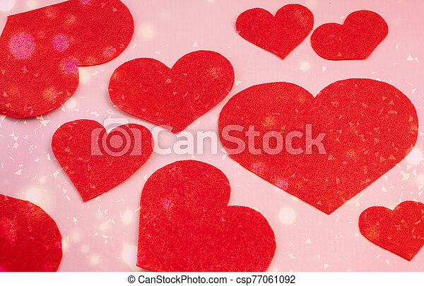 Red felt hearts on a pink paper background. Valentine's Day greeting card and romance concept. Top view, flat lay. - csp77061092