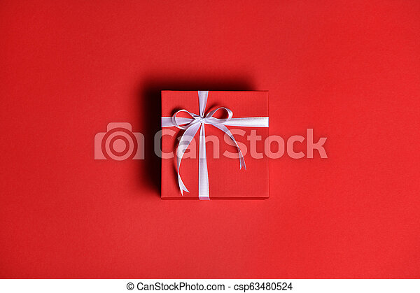 Red gift box with a white bow on red background - csp63480524