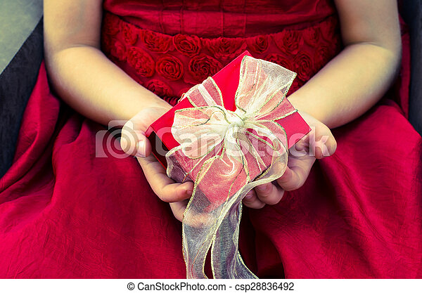 red gift box with ribbon in hands - csp28836492