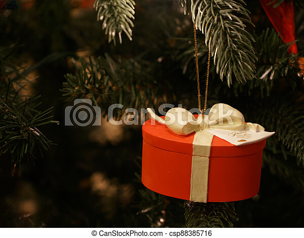 Red gift ornament on a Christmas Tree - csp88385716