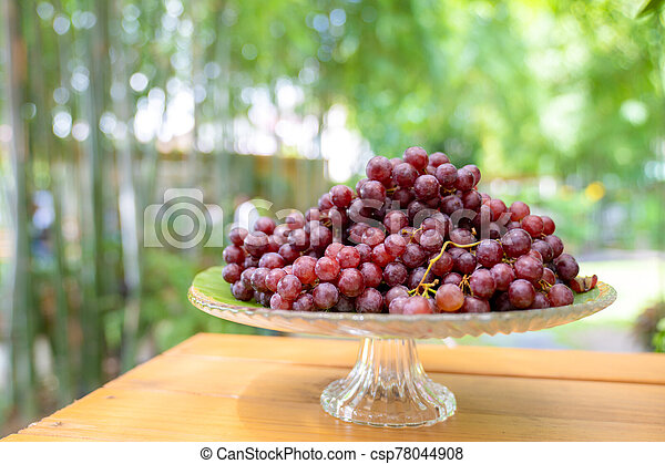 red grape on the step glass plate stand alone on the wood table in the outdoor garden field blur bokeh. - csp78044908