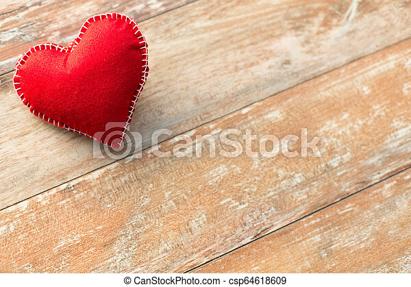 red heart shaped decoration on wooden background - csp64618609