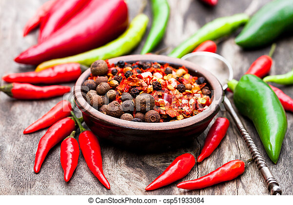 Red hot chili peppers and other spices in a small plate on wooden background - csp51933084