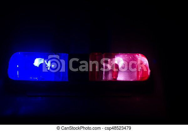 Red light flasher atop of a police car. City lights on the background. Police government concept - csp48523479