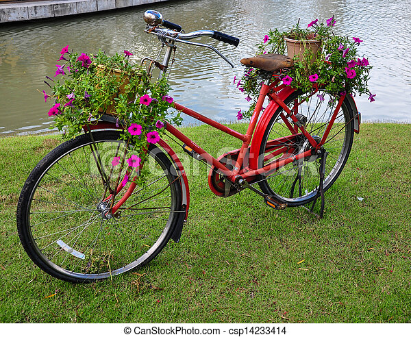 Red painted bicycle with a bucket of colorful flowers - csp14233414