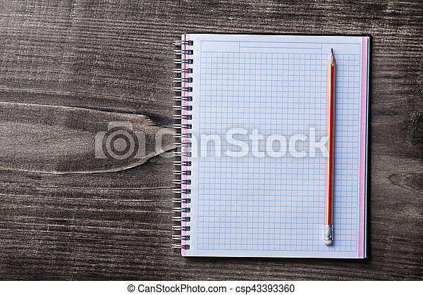 Red pencil and checked copybook on pine wooden board education c - csp43393360