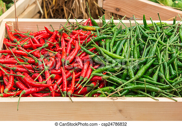 red pepper and green pepper on shelf in market. - csp24786832