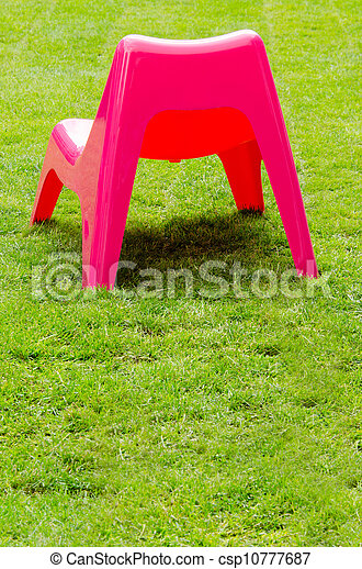 Red plastic chair on green grass - csp10777687